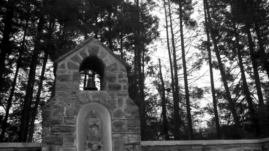 Small stone shrine with the Virgin Mary, cherub, brass and bell near wooded landscape.
